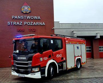 Czerowny samochód ciężarowy pożarniczy na tle Jednostki Ratowniczo-Gaśniczej w GliwicachScania_źródło KM PSP Gliwice